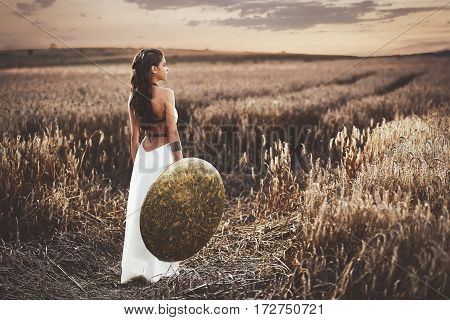 Back view of brunette girl with long hair wearing in white dress like greece style,  holding iron shield in hand. Wife waiting husband after war, among grass in field turned and looking away.