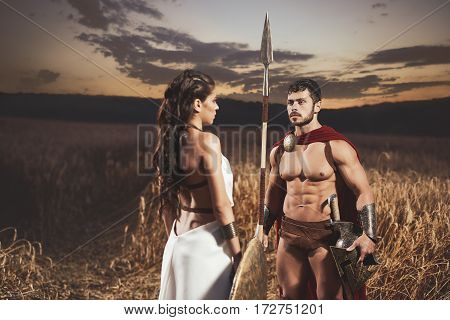 Portrait of brunette woman wearing like greece in white dress and man warrior wearing like spartan. Couple meeting after war in field at night time.