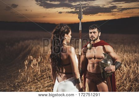 Couple meeting after war among grass in field, looking each other. Beautiful brunette woman wearing in dress like greece style holding iron shield and husband warrior wearing like spartan.