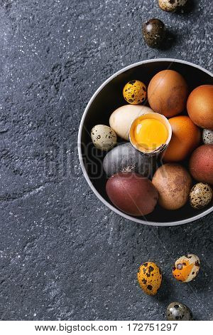 Brown and gray colored chicken and quail Easter eggs in black ceramic bowl with yolk over black concrete texture background. Top view, copy space