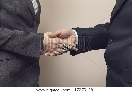 Detail of two business people sealing the deal with bribe money. Selective focus
