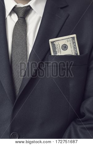 Detail of a businessman in a suit with bunch of hundred dollars banknotes in his jacket pocket. Selective focus