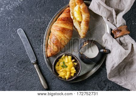Breakfast with two croissant, butter, cream and sliced mango fruit, served on serving metal tray with textile napkin and knife over black concrete texture background. Top view with space.