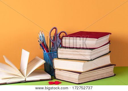 Open book hardback books and magnifying glass on bright colorful background. Back to school. Copy space for text