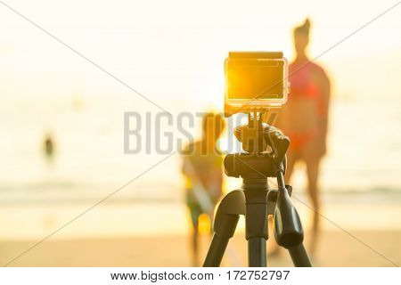Action compact camera on a tripod to take photos and video of people on the beach during sunset.