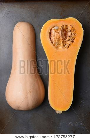 High angle view of a Butternut Squash cut in half on a metal baking sheet.