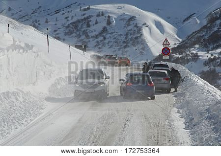 BRIANCON, FRANCE - FEBRUARY 1, 2015 : Cars in a blizzard on an mountain pass. Severe winter weather causes difficulties on the roads.