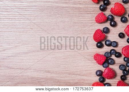 Copyspace of red ripe raspberry and blueberries lies on a wooden background. Copyspace flat lay top view. Macro