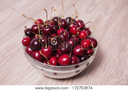 Ripe juicy red cherry with drops of water in a transparent plate on a wooden background. Cherry on a background of wood