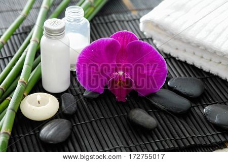 Spa setting on mat with bamboo grove, oil,candle ,orchid on towel