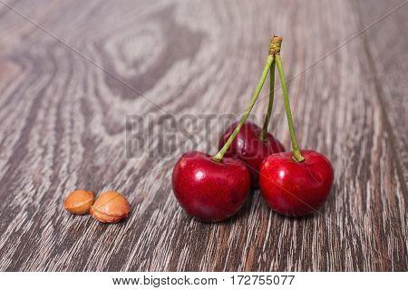 Three red ripe juicy cherries and bones lying on vintage wooden background. Sweet summer berries. Macro photography of juicy cherries