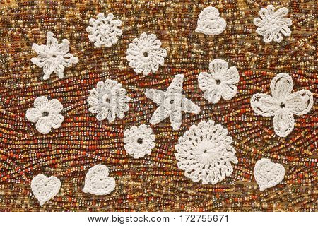A heap of beads and whote Irish crochet flowers hearts and stars. Creative craft artwork