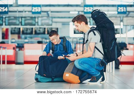 Two friends traveling by airplane. Travelers preparing their passports and airplane ticket at the airport check-in.