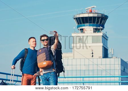 Two friends traveling together. Travelers taking a selfie at the airport. Prague Czech Republic.