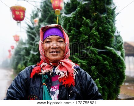 CHIANG RAI THAILAND - JANUARY 06 2017: Unidentified Akha indigenous hill tribe portrat with morning mist at local street of Mae Salong street market.
