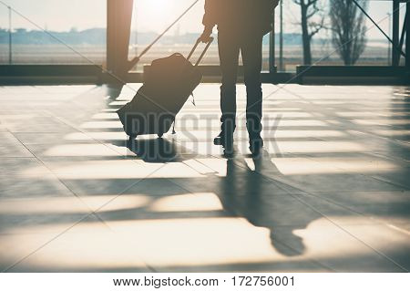 Shadow of the traveler with luggage at the airport.