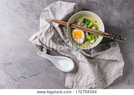 White bowl of asian style soup with scrambled eggs, half of marinated egg, spring onion, spinach served with wood chopsticks, spoons, textile over gray texture background. Top view with space