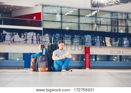 Two friends traveling together. Travelers with mobile phones waiting at the airport departure area for their delay flight.