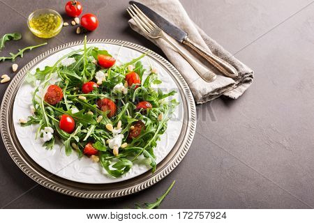 fresh vegetable salad with rucola, tomatos and goat cheese. Healthy food concept. Copy space.