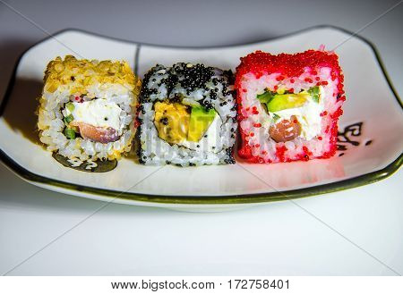 Three sushi on a white plate standing on the white glass