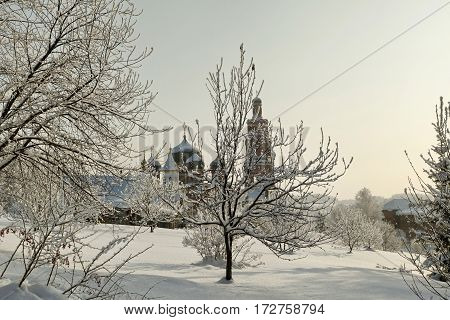 Orthodox Monastery Behind Bare Trees In Deep Snow At Winter