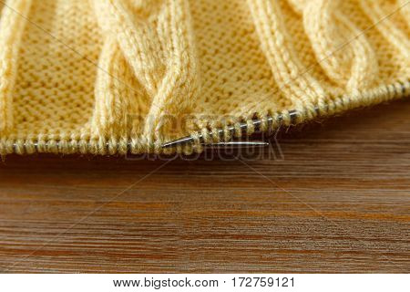 Yellow Knitted Work in ProcessGrey Knitting Needles.Hand Made;Fancywork.Wooden Background