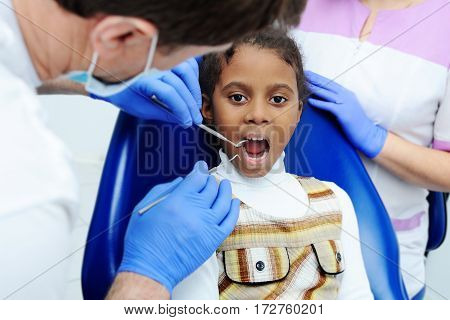portrait of an African baby girl with black skin in the dental chair. The dentist examines the mouth and teeth of a young child