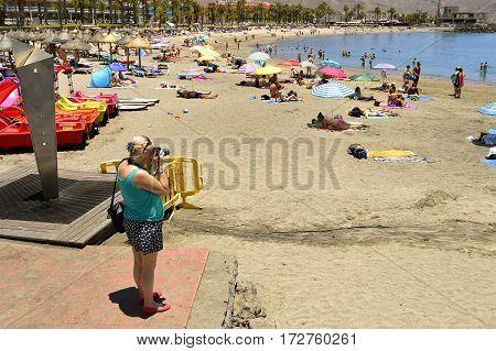 Playa De Las Americas beach Tenerife Canary Islands Spain Europe - June 12 2016: Photographer on the beach taking photographs