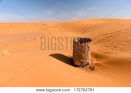 View over the dunes of Erg Chebbi desert near Merzouga in Morocco with a dry water well in the foreground.