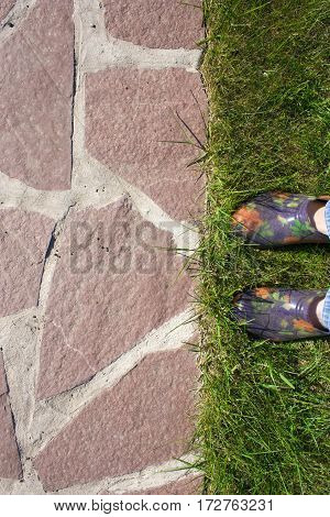 background on the garden path of natural stone lawn and feet in rubber galoshes