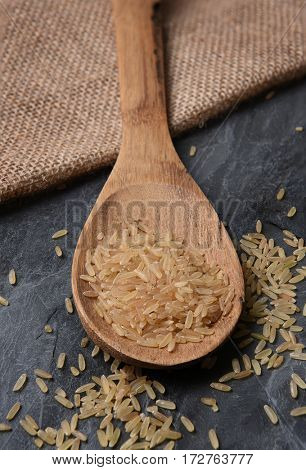 Closeup of a wood spoon with brown rice, on a slate background and burlap sack.