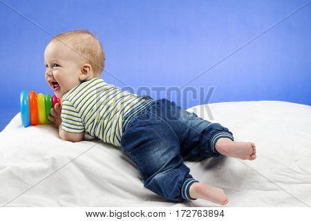 Laughing little baby boy, sitting on the white blanket with a toy in hands , studio shot, isolated on blue background.