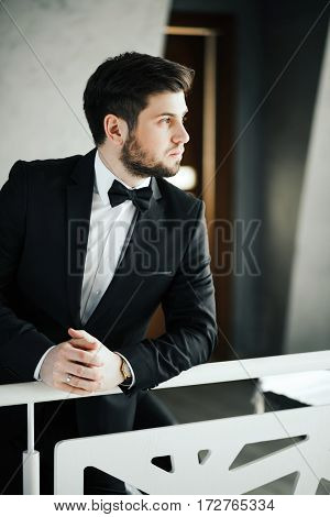 Handsome bridegroom with dark hair wearing black costume looking right, portrait, copy space.