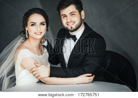 Lovely wedding photo, brunette bride and bridegroom sitting together at gray background and holding hands, smiling.