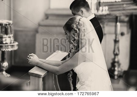 Bride And Groom Pray Standing On The Knees During An Engagement Ceremony