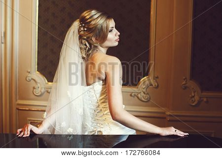 A Profile Of A Gorgeous Blonde Bride Leaning On  Black Piano