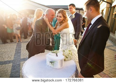 Bride Hugs An Old Man While She Stands On A Backyard With A Groom