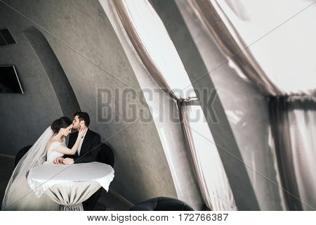 Gorgeous bride and bridegroom sitting close to each other at big window at background, wedding photo.