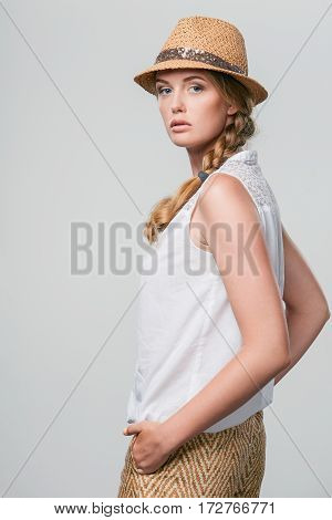 Calm woman wearing summer straw fedora hat looking at camera over shoulder