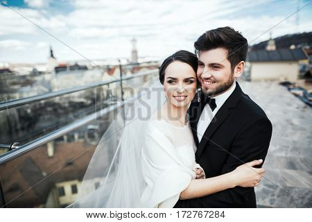 Gorgeous brunette bride and bridegroom standing close to each other at old city background and smiling, wedding photo.