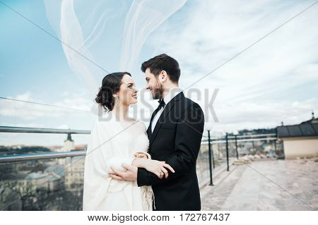 Beautiful brunette bride and bridegroom standing close to each other at old city background and smiling, wedding photo, copy space.