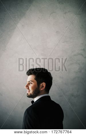 Handsome bridegroom standing at gray background, looking left, copy space, portrait.