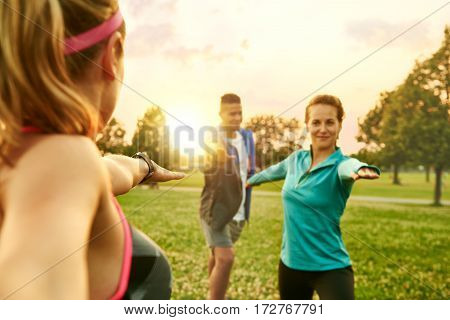 Female fitness coach leading her group in a strength training session with the sunlight behind. Sunset golden tone filter
