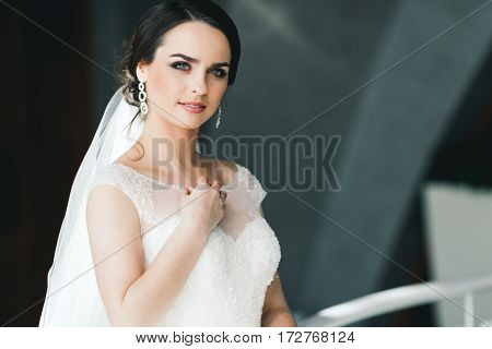 Beautiful bride with black hair and big eyes wearing white dress at gray background, looking right and smiling, portrait.