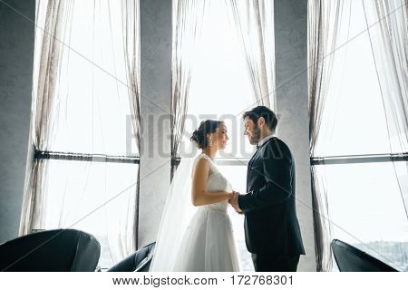 Gorgeous  brunette bride and bridegroom standing close to each other and holding hands at big window at background, wedding photo, copy space.