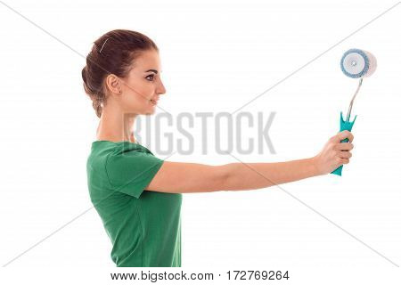 profeil of young pretty brunette woman builder in uniform with paint roller in hands make reovations isolated on white
