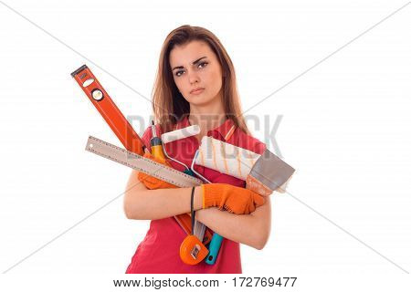 young tired brunette woman builder in uniform with tools in her hands make reovations isolated on white