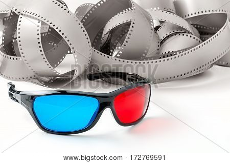 3d glasses and vintage movie film on a white background