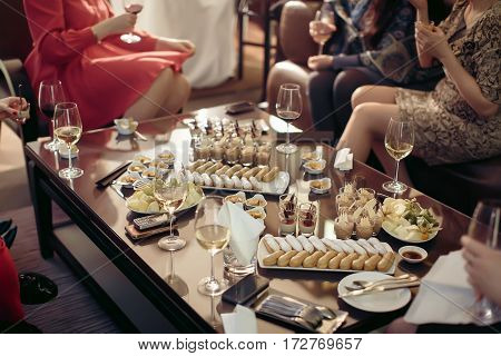 Bachelorette party dessert table with wine eclairs with women's legs