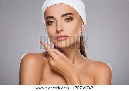 Young girl with brown hair fixed behind, clean fresh skin, big eyes and naked shoulders wearing white bandage, posing at gray studio background with cleaning sponge near face, close up.